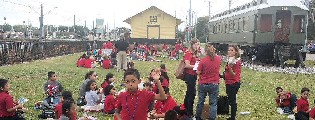 Students in grassy area between Landmark Museum and Pullman Coach Car.